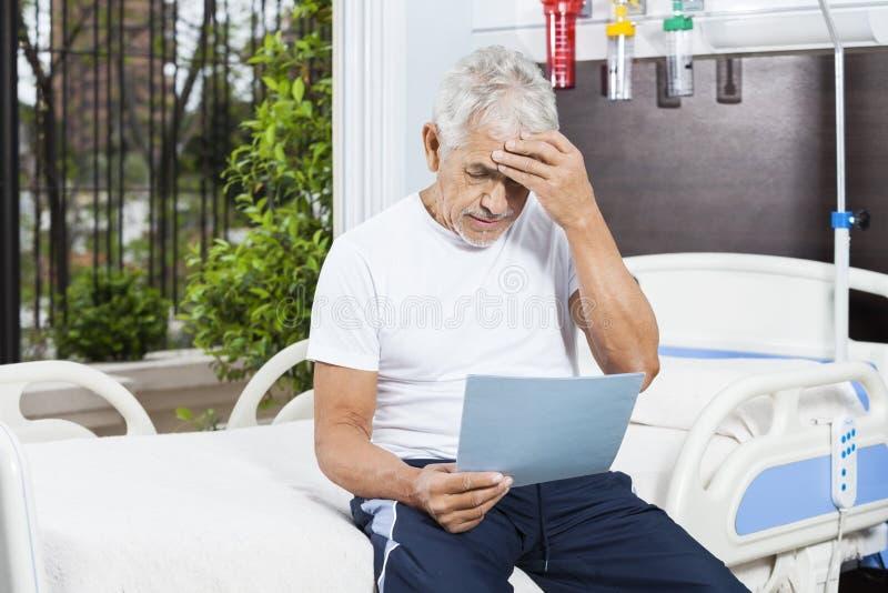 Rapporti tesi della lettura dell'uomo senior nel centro di riabilitazione fotografia stock