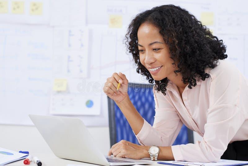 Rapporto della lettura della donna di affari sul computer portatile immagini stock