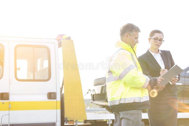 Rapporto di firma della donna di affari mentre parlando per rimorchiare autista di camion contro il cielo fotografia stock libera da diritti