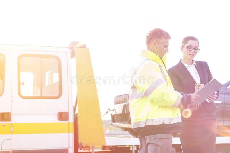 Rapporto di firma della donna di affari mentre parlando per rimorchiare autista di camion contro il cielo immagine stock