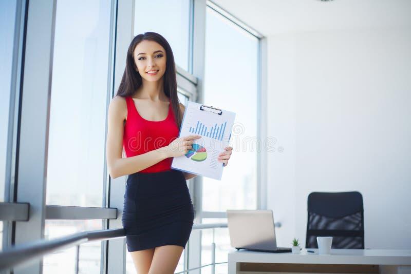 Rapporto femminile sorridente del grafico di profitto di rappresentazione del venditore immagini stock