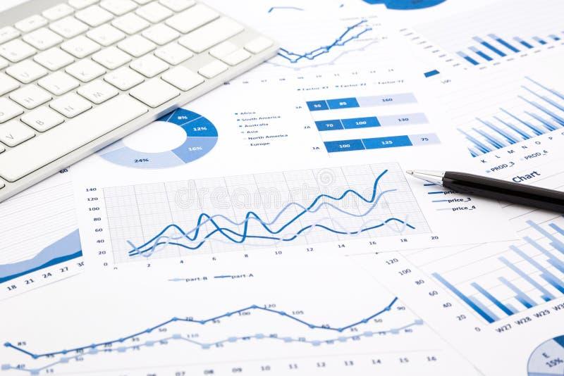 Rapports bleus de graphique et de diagramme sur la table de bureau photographie stock libre de droits