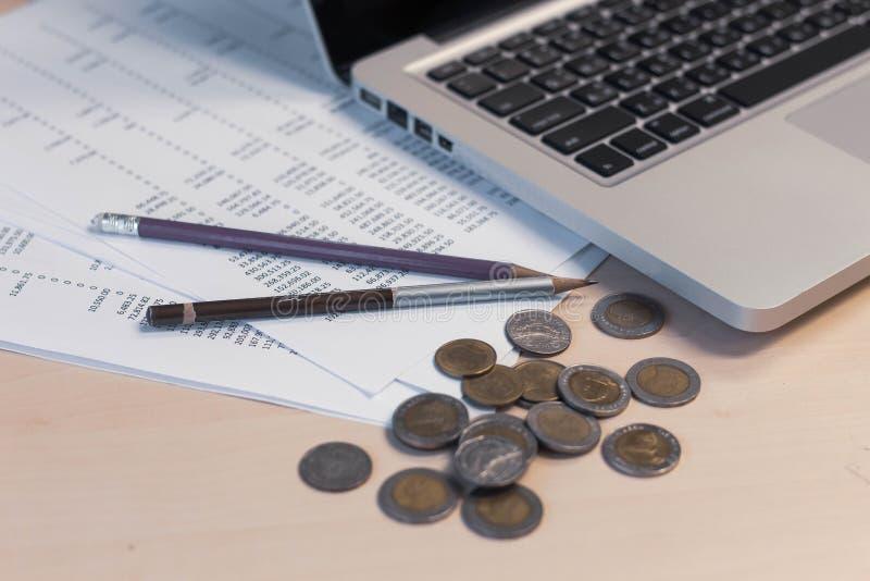 Rapports financiers et pièces de monnaie avec l'ordinateur photo libre de droits