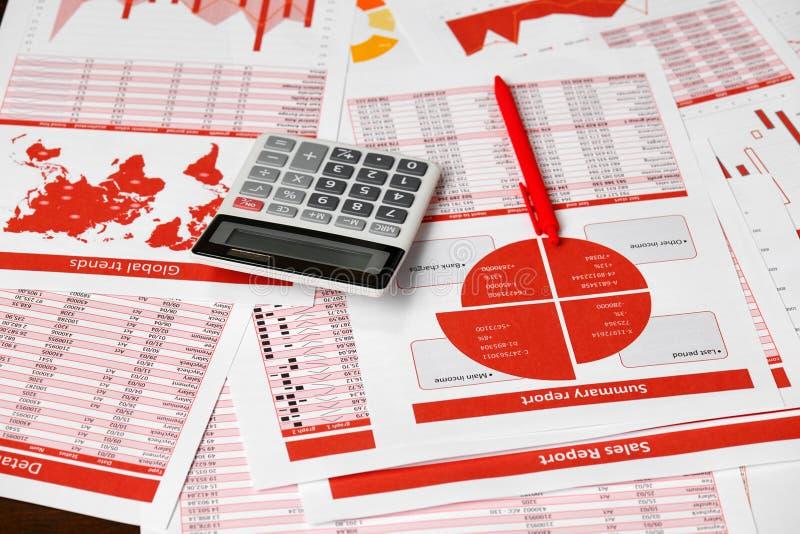 Rapports, graphiques et calculatrice rouges pour calculer des finances sur le bureau de bureau concept de comptabilité financière photos stock