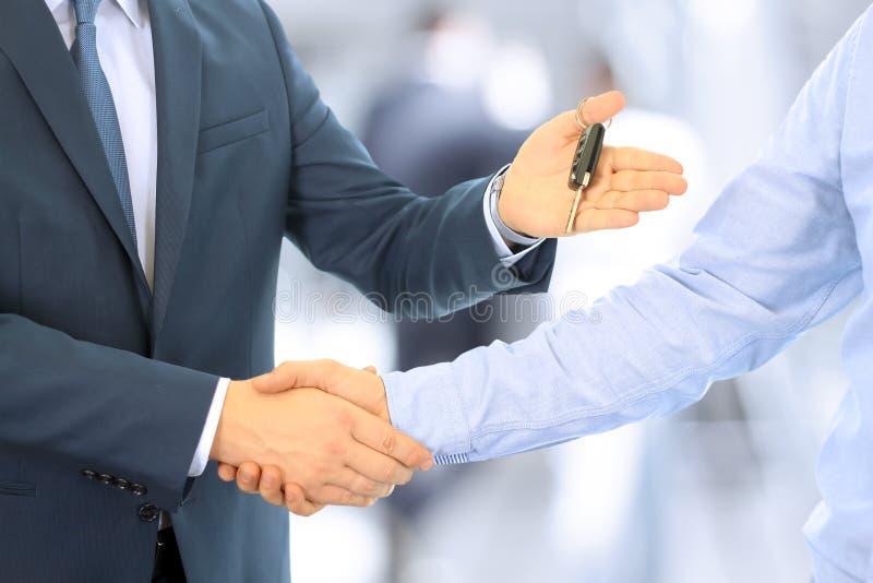 Rappresentante di automobile che consegna le chiavi per una nuova automobile ad un giovane uomo d'affari Stretta di mano fra due  immagine stock