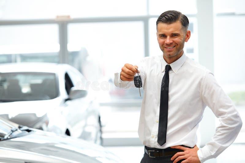 Rappresentante di automobile Giving Key di nuova automobile alla sala d'esposizione fotografie stock