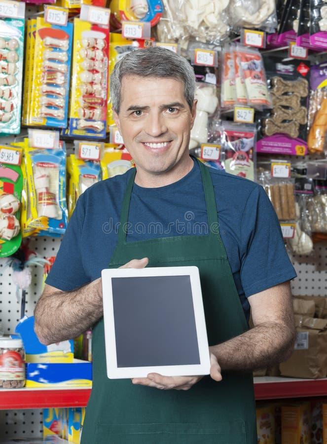 Rappresentante Showing Digital Tablet con lo schermo in bianco nel deposito dell'animale domestico fotografia stock