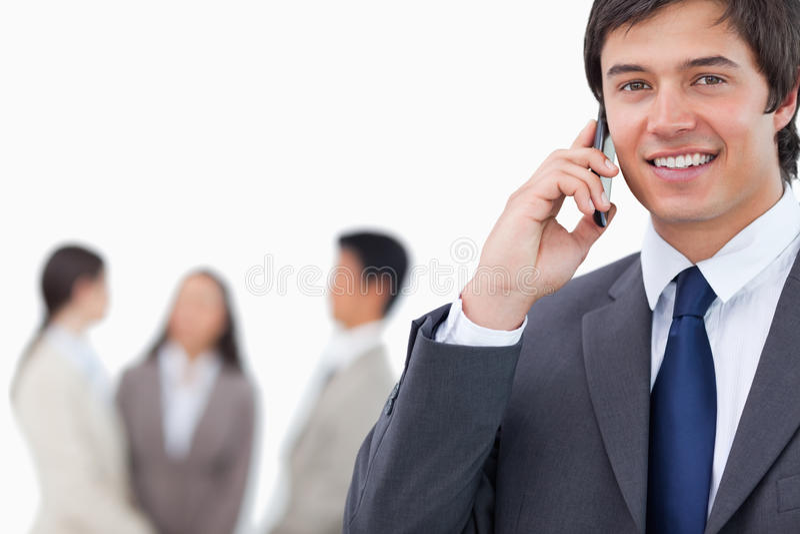 Rappresentante sorridente sul suo cellulare con il gruppo dietro lui immagini stock libere da diritti