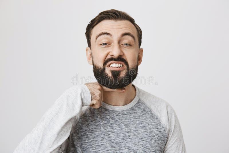 Rappresentazione barbuta arrabbiata del tipo vi taglierò dirigo fuori il gesto con il dito indice sopra il collo, controllante il fotografia stock libera da diritti