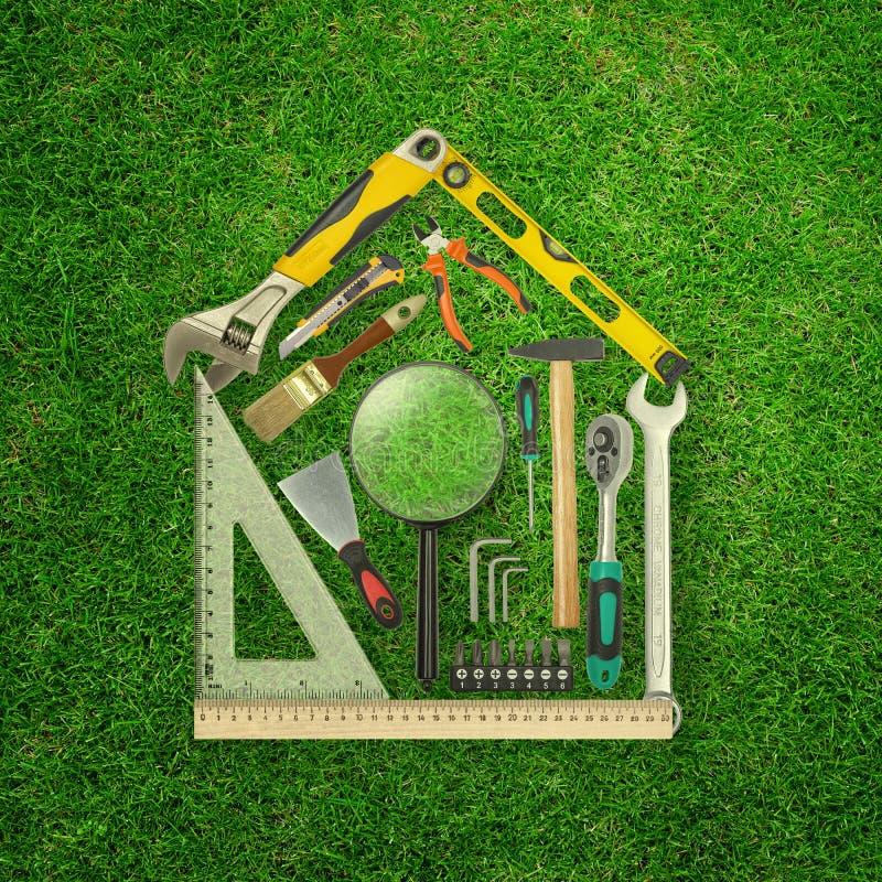 rappresentazione 3d dell'insieme degli strumenti della costruzione a forma di come casa sul fondo dell'erba verde fotografie stock libere da diritti