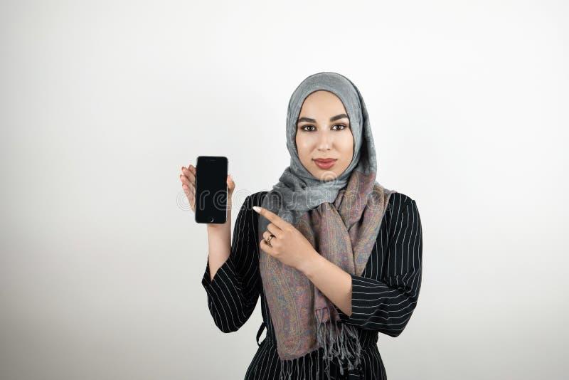 Rappresentazione d'uso del foulard del hijab del turbante del giovane studente musulmano attraente ed indicare allo smartphone co fotografia stock