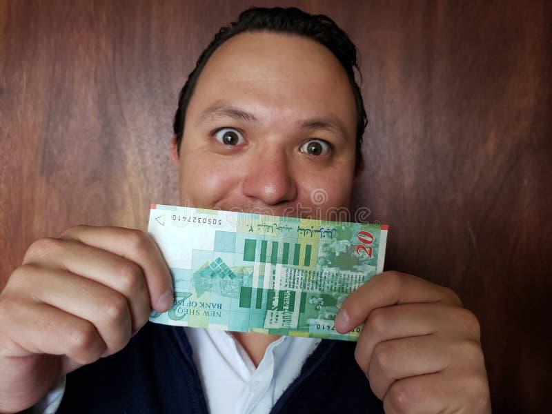 rappresentazione del giovane e tenere una banconota israeliana di venti shekel immagini stock libere da diritti