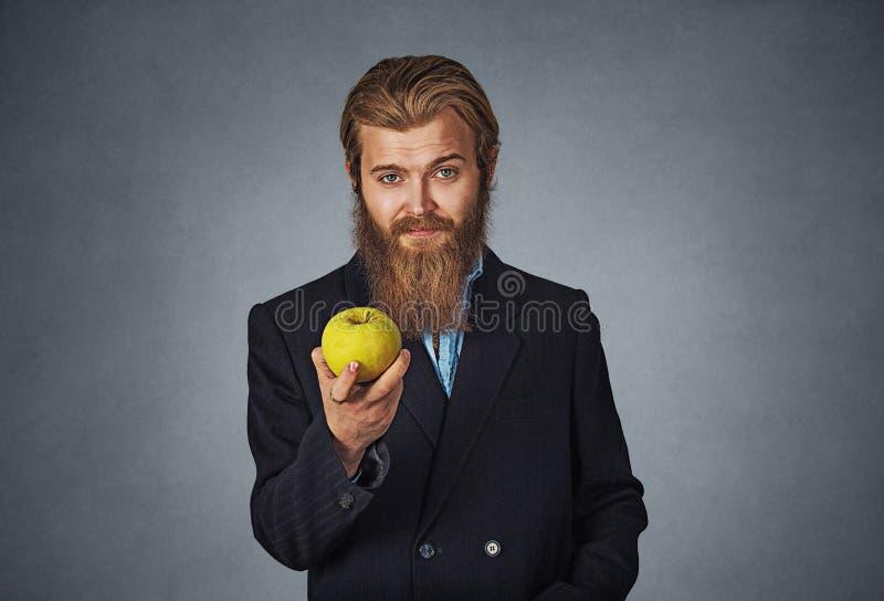 Rappresentazione dell'uomo d'affari che dà tenendo una mela verde in sua mano fotografie stock libere da diritti