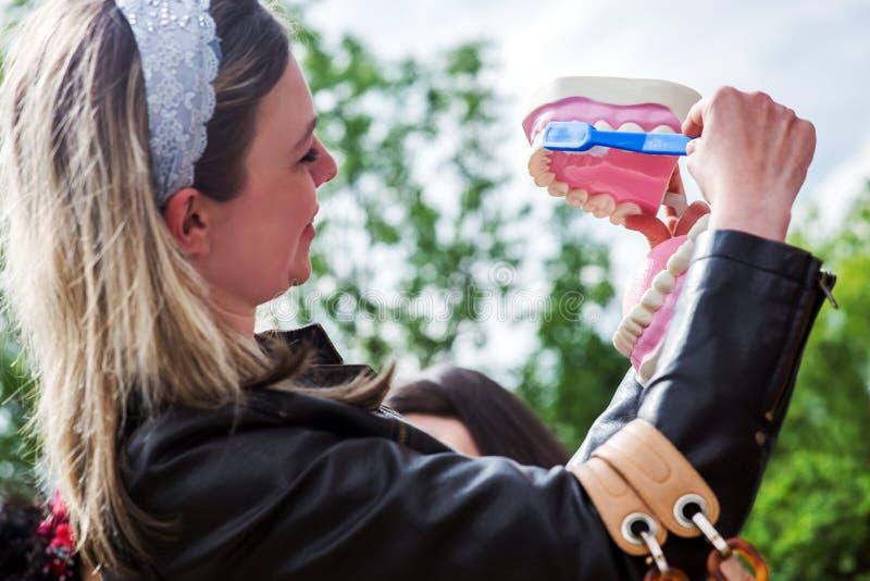 Rappresentazione della donna come pulire correttamente i denti con lo spazzolino da denti e radrizzare fotografia stock libera da diritti