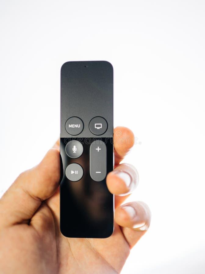 Rappresentazione della mano dell'uomo che tiene il fondo bianco telecomandato di Apple TV 4k fotografia stock