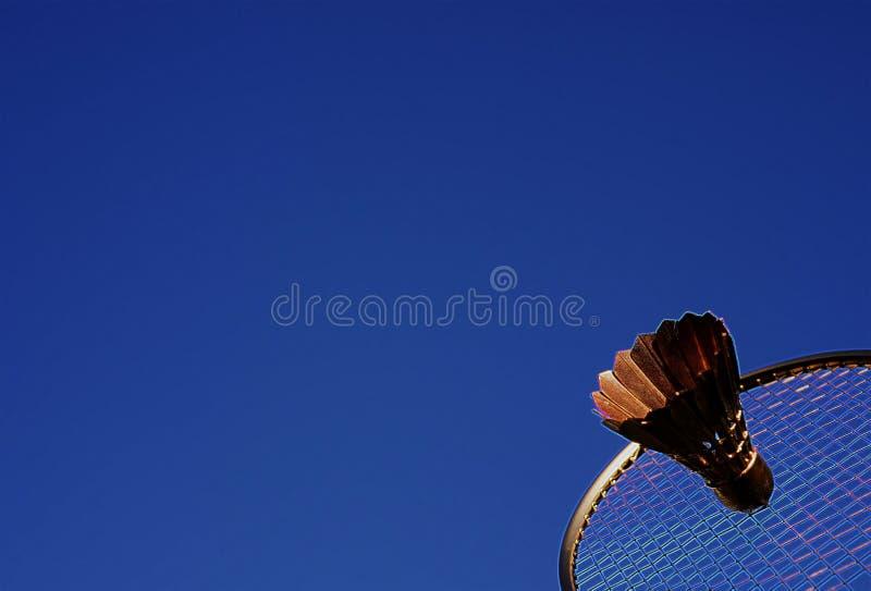 Raquete de badminton e azul-céu abstratos coloridos da peteca fotografia de stock royalty free