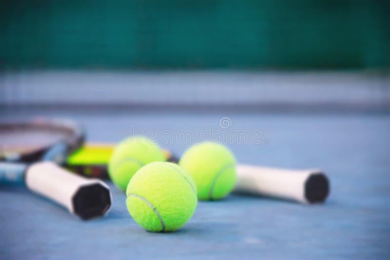 Raquete de tênis com a bola na corte dura azul com ninguém imagens de stock