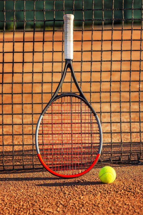 Raquete de tênis com uma bola perto da rede na corte de terra Dia ensolarado Close-up fotos de stock