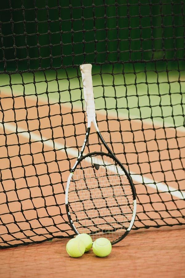 Raquete de tênis e 3 bolas no close-up da grade do campo de tênis Equipamento de esportes imagem de stock royalty free
