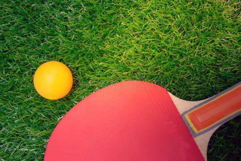 A raquete de tênis de mesa e a bola alaranjada, tênis de mesa remam no greensward imagem de stock