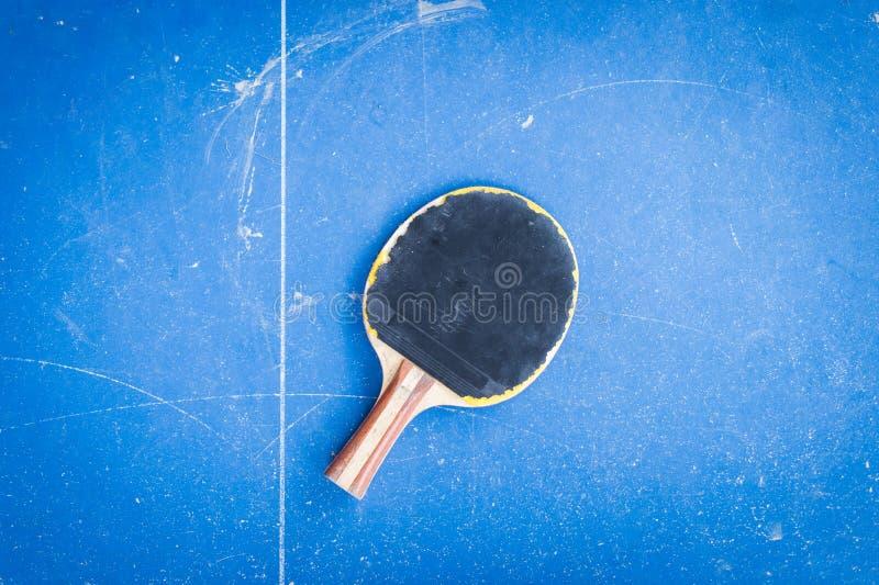 Raquete do tênis de mesa na tabela azul fotografia de stock royalty free