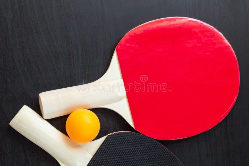 Raquetes e bola do pong do tênis de mesa dois ou do sibilo em um fundo preto fotos de stock