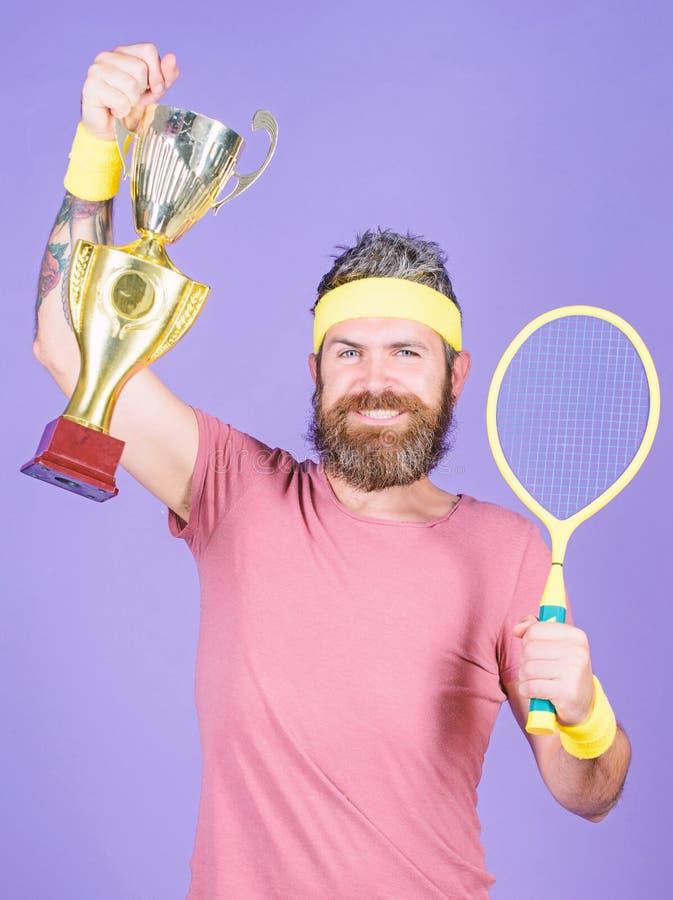 Raquette de tennis de prise d'athl?te et gobelet d'or ?quipement barbu de sport d'usage de hippie d'homme Succ?s et accomplisseme photos libres de droits
