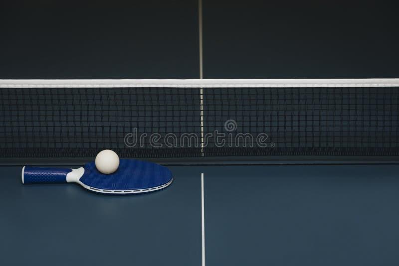 Raquettes de ping-pong et boule et filet sur une table de ping-pong bleue photographie stock
