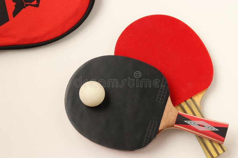 Raquettes rouges et noires pour jouer au ping-pong sur un fond blanc, vue sup?rieure photos stock