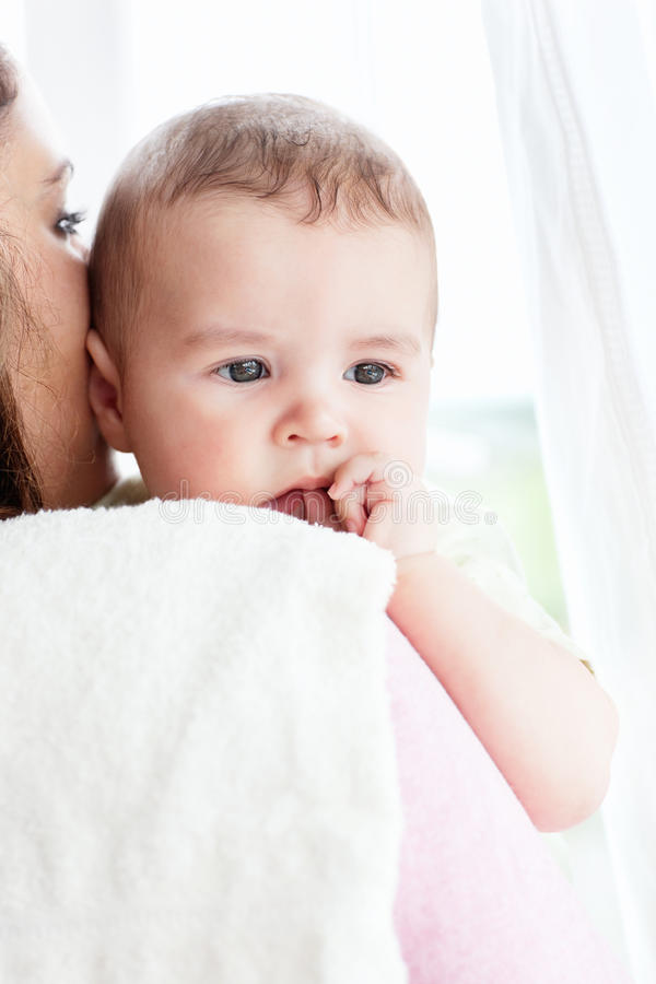 Rar view of a mother holding her baby. At home royalty free stock image