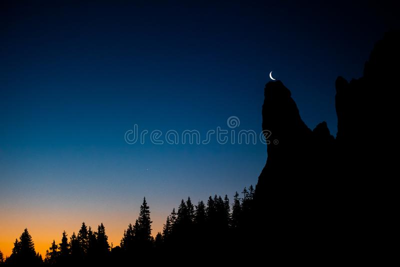 Rarau Mountain at blue hour with new moon , Pietrele Doamnei peek. Forest silhouette stock photos