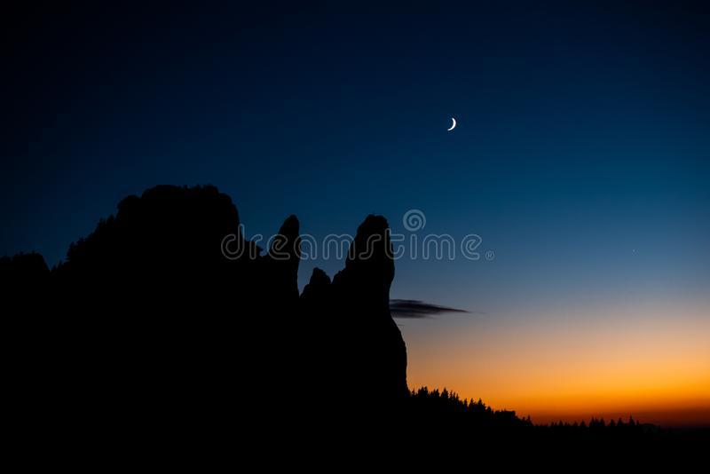 Rarau Mountain at blue hour with new moon , Pietrele Doamnei peek. Forest silhouette royalty free stock image