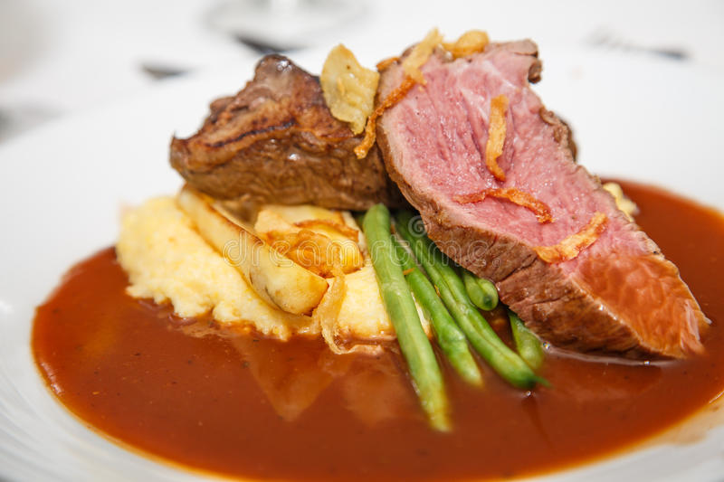 Rare Beef with Green Beans and Potatoes. Sliced rare beef on a plate with gravy, green beans and potatoes stock photos