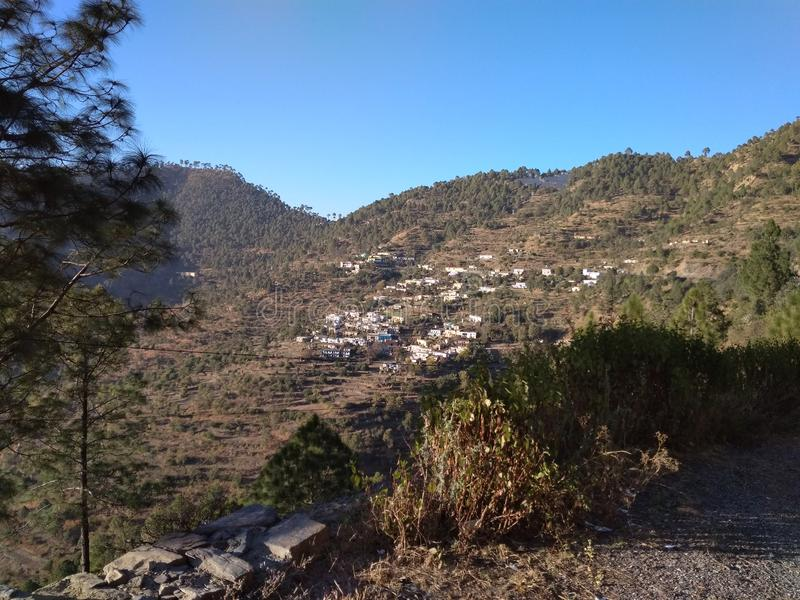 A Rare Distant Snapshot of a Remote Village in Tehri District. The rare snapshot of a remote village surrounded by the green forest hills with a clear blue sky royalty free stock photos