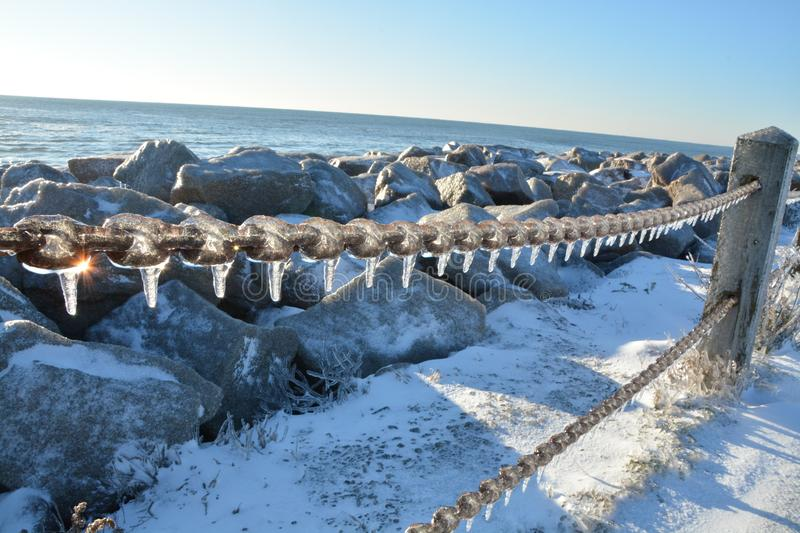 Cold shores in the carolinas. A rare snow and ice storm in Kure Beach North Carolina covers the rocks royalty free stock image