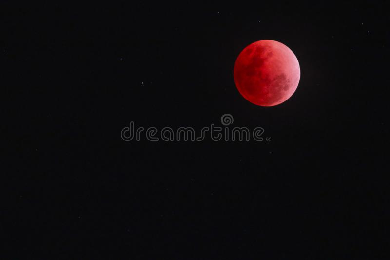 Blood moon over southern thailand against black sky with a few stars. The rarely present blood moon that was visible over southern thailand on 31 january 2018 royalty free stock image
