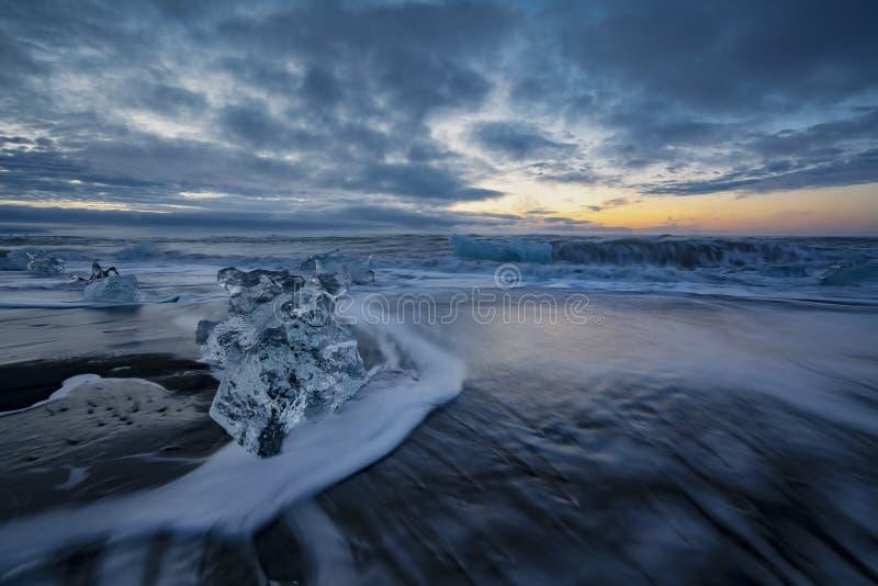 Rasa vågor som slår iskvarter på soluppgång på Diamond Beach arkivbilder