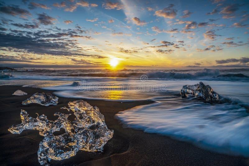 Rasa vågor som slår iskvarter på soluppgång på Diamond Beach royaltyfria foton