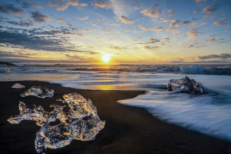 Rasa vågor som slår iskvarter på soluppgång på Diamond Beach royaltyfria bilder