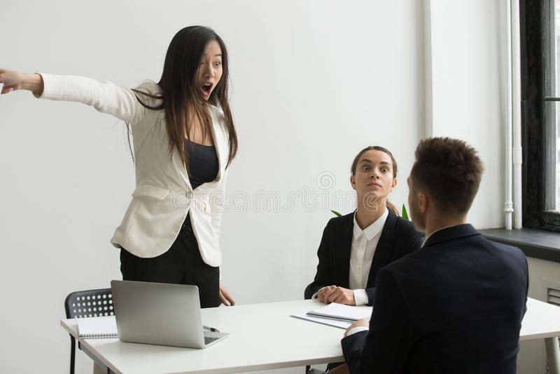 Rasande affärskvinna som är ilsken på affärsmannen som berättar att lämna mult royaltyfri foto