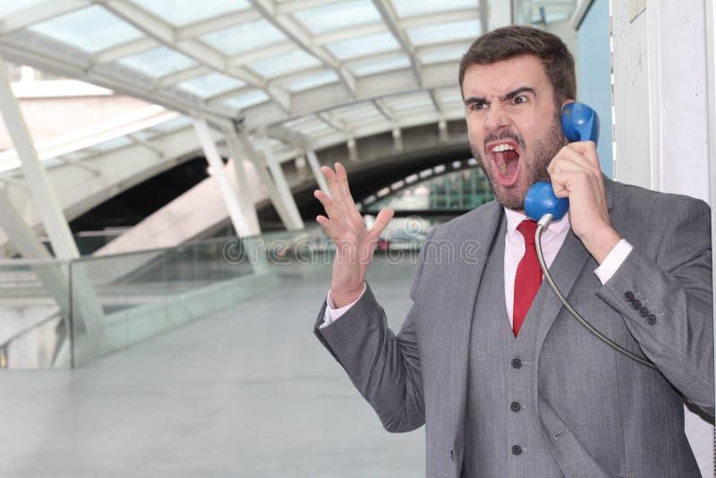 Rasande affärsman som skriker på den offentliga telefonen royaltyfri foto