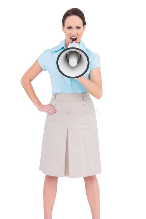 Rasande flott affärskvinna som talar i megafon arkivbild