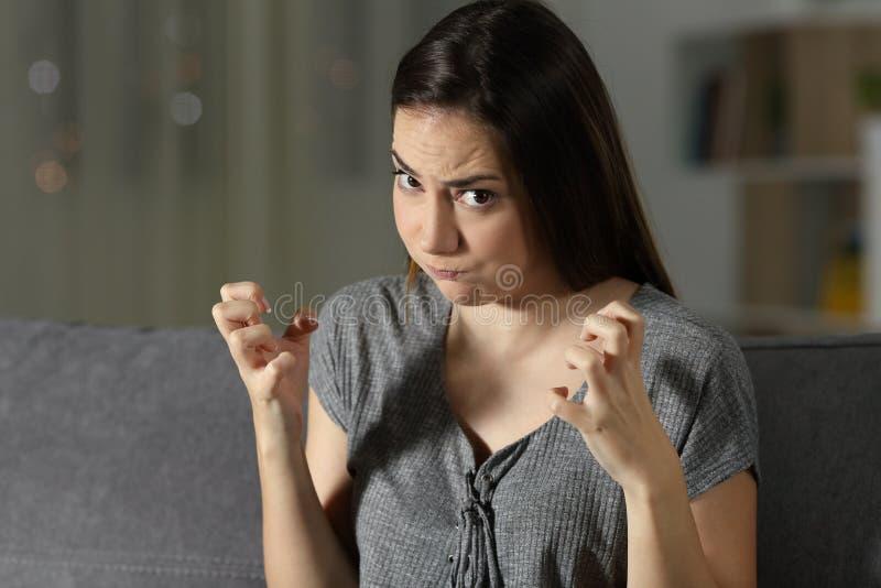 Rasande kvinna som hemma ser kameran i natten royaltyfria bilder
