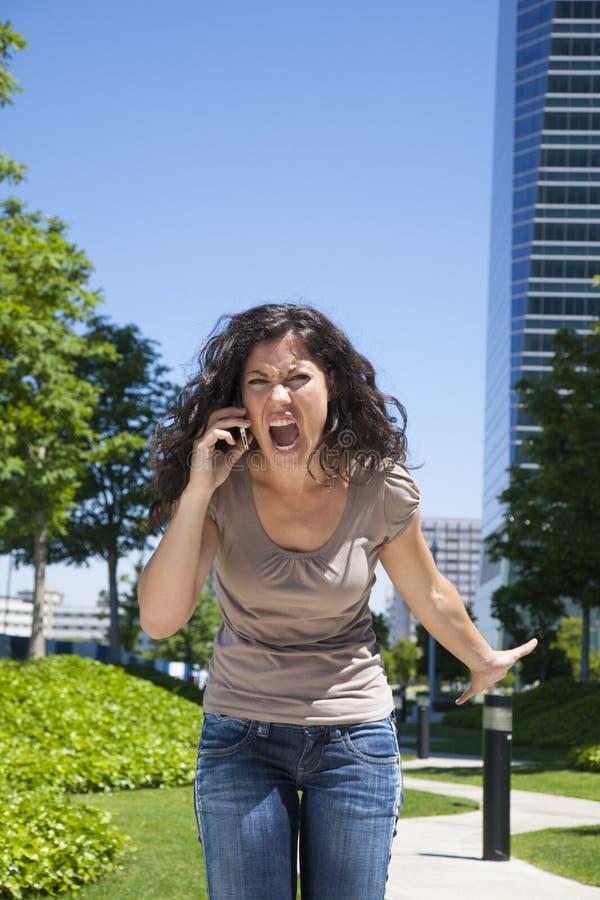 Rasande kvinna som ropar telefonen royaltyfri bild