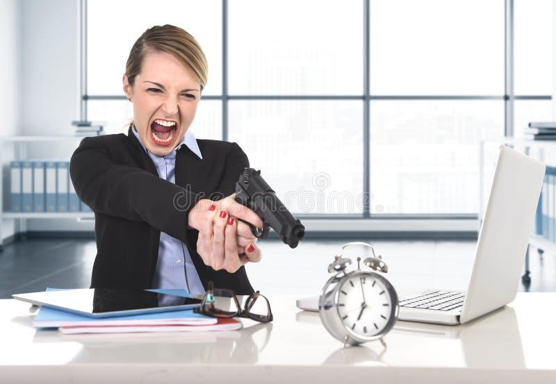 Rasande och ilsket arbete för affärskvinna med datorbärbara datorn som pekar vapnet till ringklockan royaltyfri bild