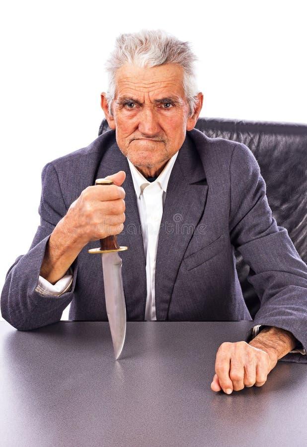 Rasande pensionär med en kniv som ser kameran royaltyfri fotografi