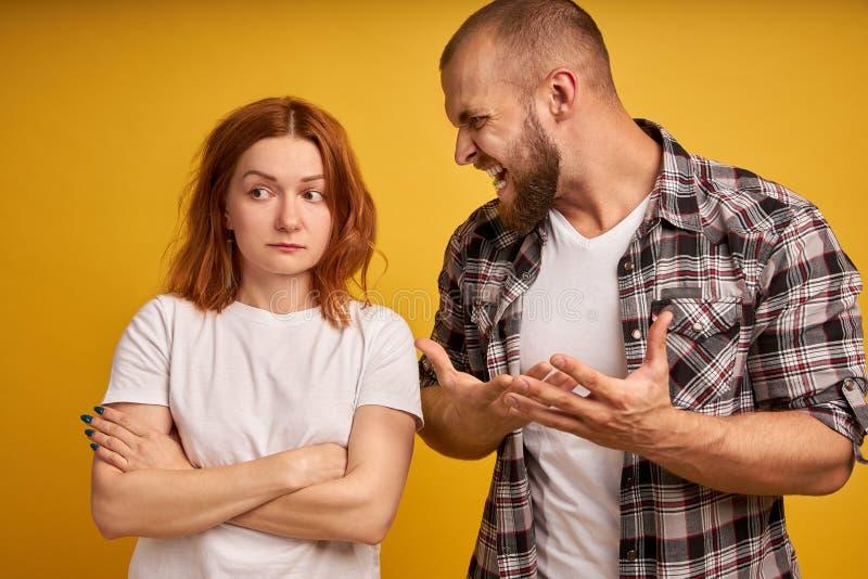 Rasande skäggiga grabbskrin och gester angrily, skrän på kvinnan, har tvist, poserar tillsammans över gul bakgrund str?ngt framst royaltyfria foton