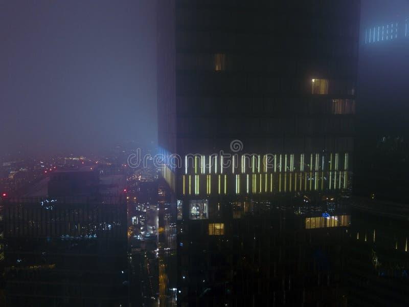 Rascacielos en la ciudad en la niebla en la noche de una foto del abejón de la altura foto de archivo