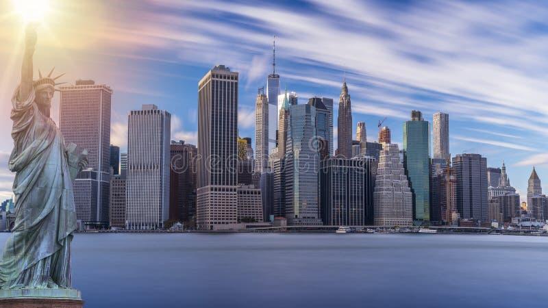 Rascacielos modernos en New York City con la estatua de la libertad fotos de archivo