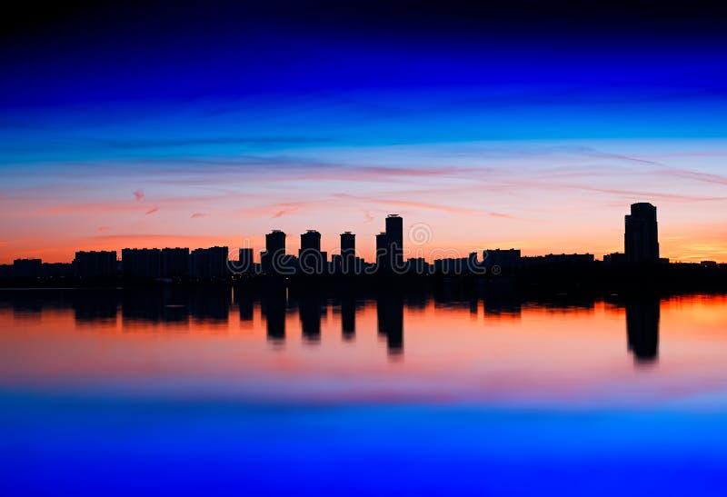 Rascacielos que hacen frente al fondo ardiendo de la puesta del sol imagen de archivo